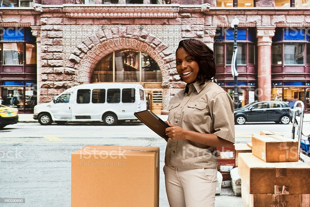 Cheerful delivery person using tablet outdoors stock photo