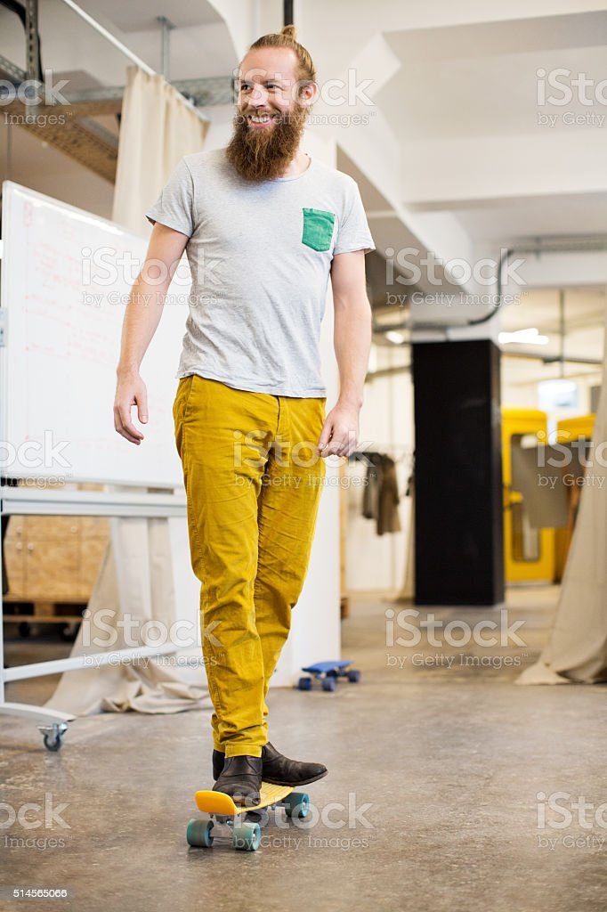 Cheerful designer skating through his office stock photo