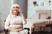 Cheerful disabled senior woman talkign on smart phone