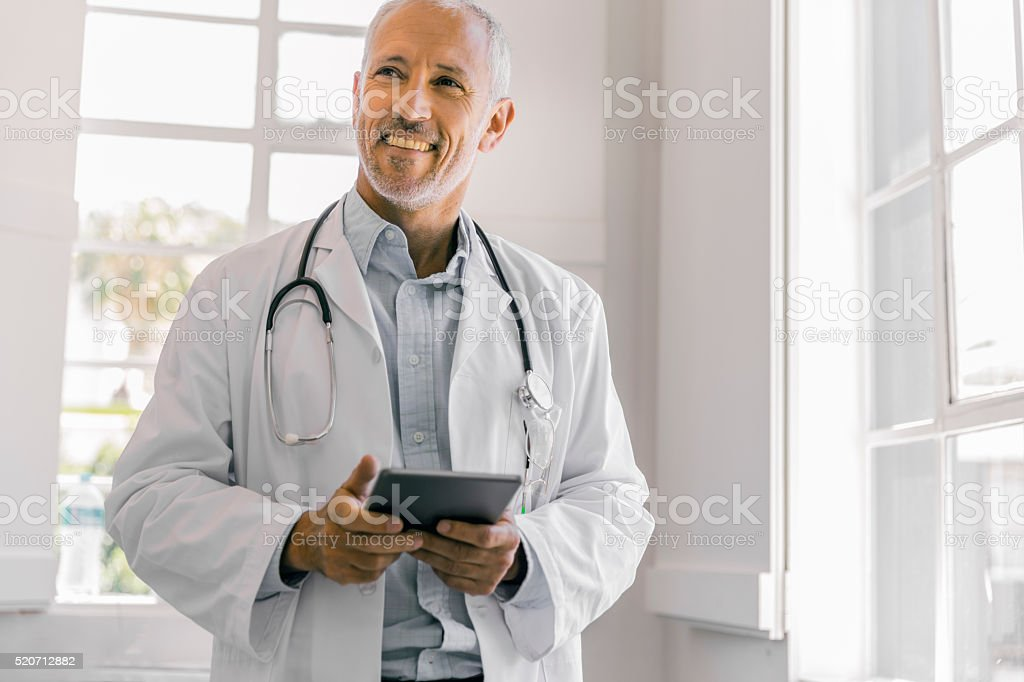 Cheerful doctor holding digital tablet in clinic stock photo