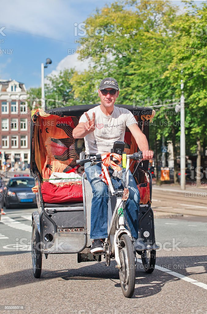 Cheerful driver of an awesome bicycle taxi in Amsterdam stock photo