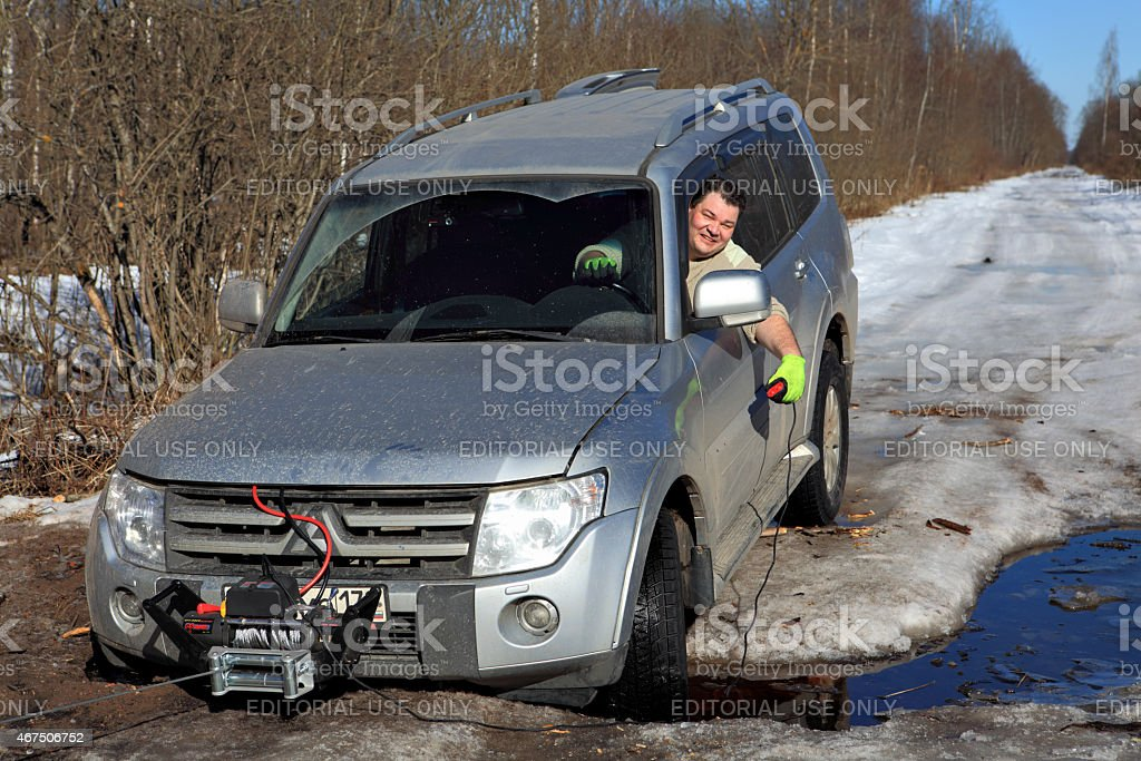 cheerful driver pulls car out of hole with winch stock photo