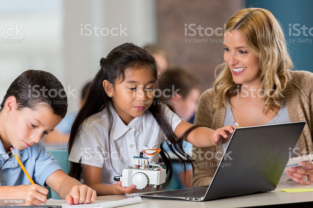 Cheerful elementary STEM school teacher helps students with assisngment stock photo