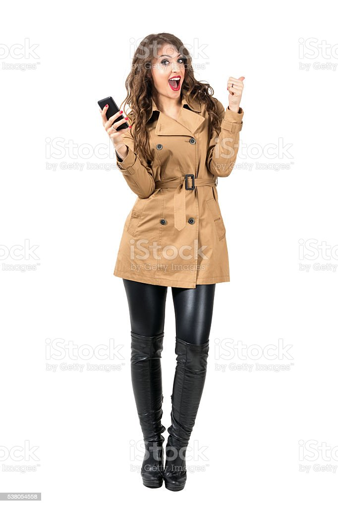 Cheerful excited woman holding mobile phone with thumbs up gesture stock photo