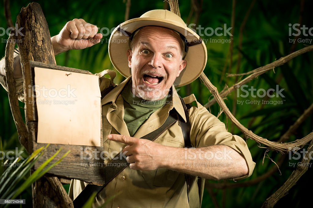 Cheerful explorer pointing to a sign stock photo