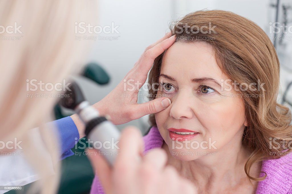 Cheerful eye doctor is working with a patient stock photo