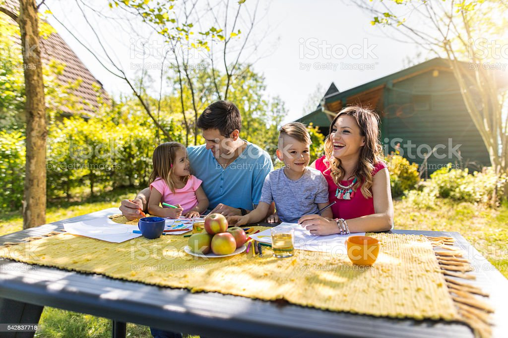 Cheerful family coloring together in their backyard and laughing. stock photo