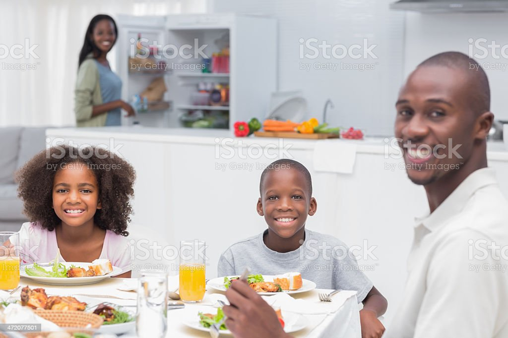 Cheerful family having dinner together looking at camera with mo royalty-free stock photo