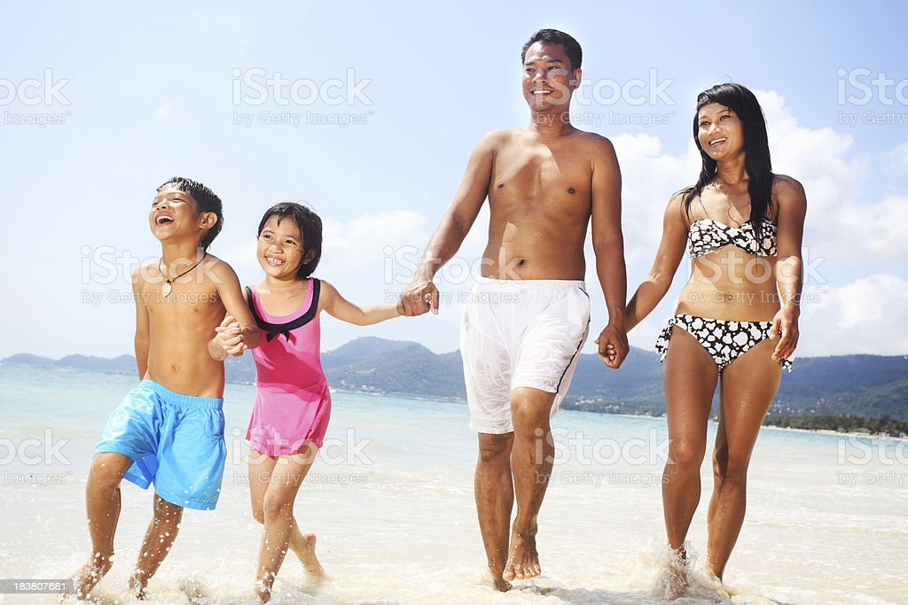 Cheerful family holding hands and walking on the beach royalty-free stock photo