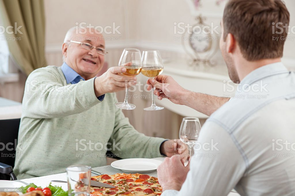 Cheerful family is celebrating with alcohol drink stock photo