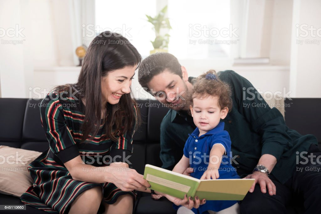 Cheerful family looking at child book at home stock photo
