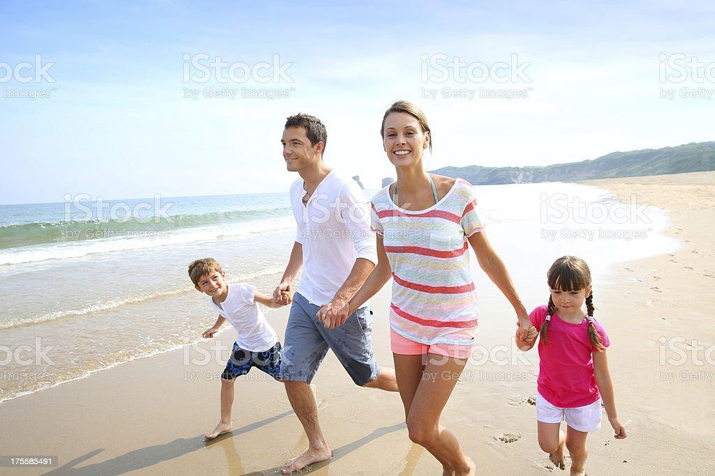 Cheerful family running on a sandy beach stock photo