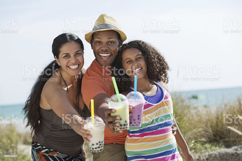 Cheerful Family Showing Bubble Teas At Beach stock photo
