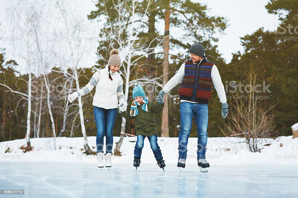 Cheerful family skating in park stock photo