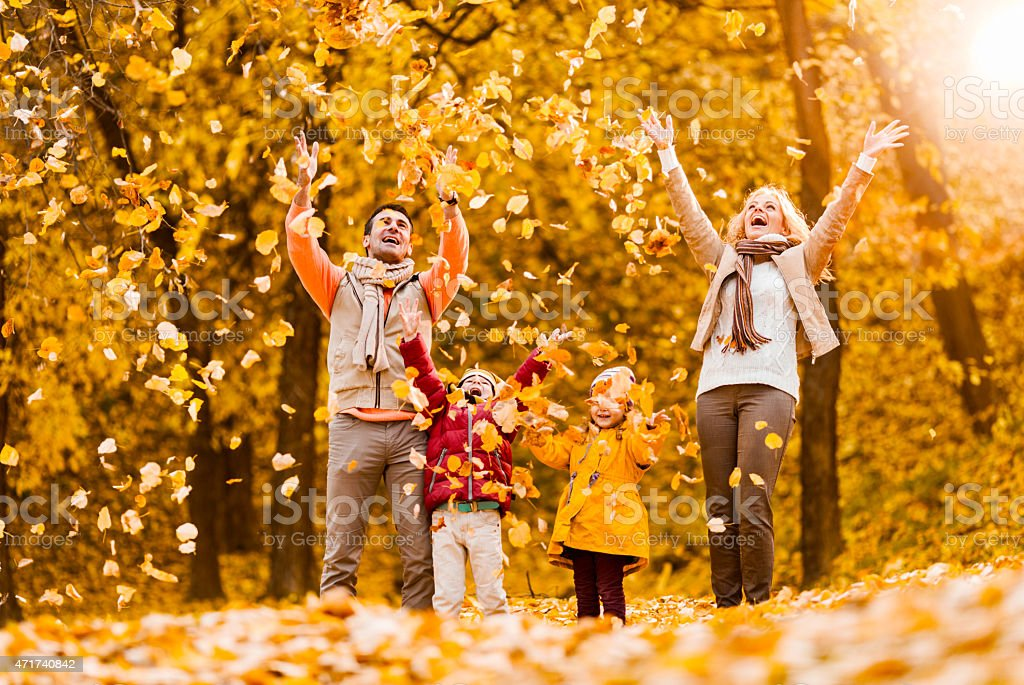 Cheerful family throwing autumn leaves in the park. stock photo