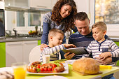 Cheerful family using digital tablet during breakfast