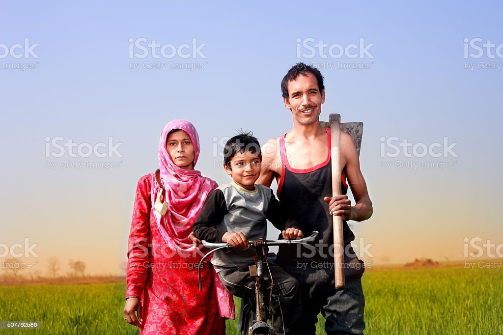 Cheerful Family with Bicycle standing in the field Portrait stock photo