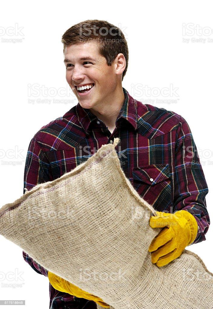 Cheerful farmer holding burlap sack stock photo