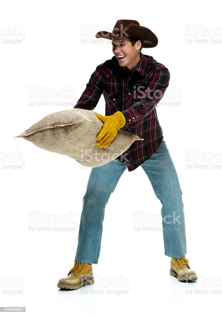 Cheerful farmer picking up a burlap sack stock photo