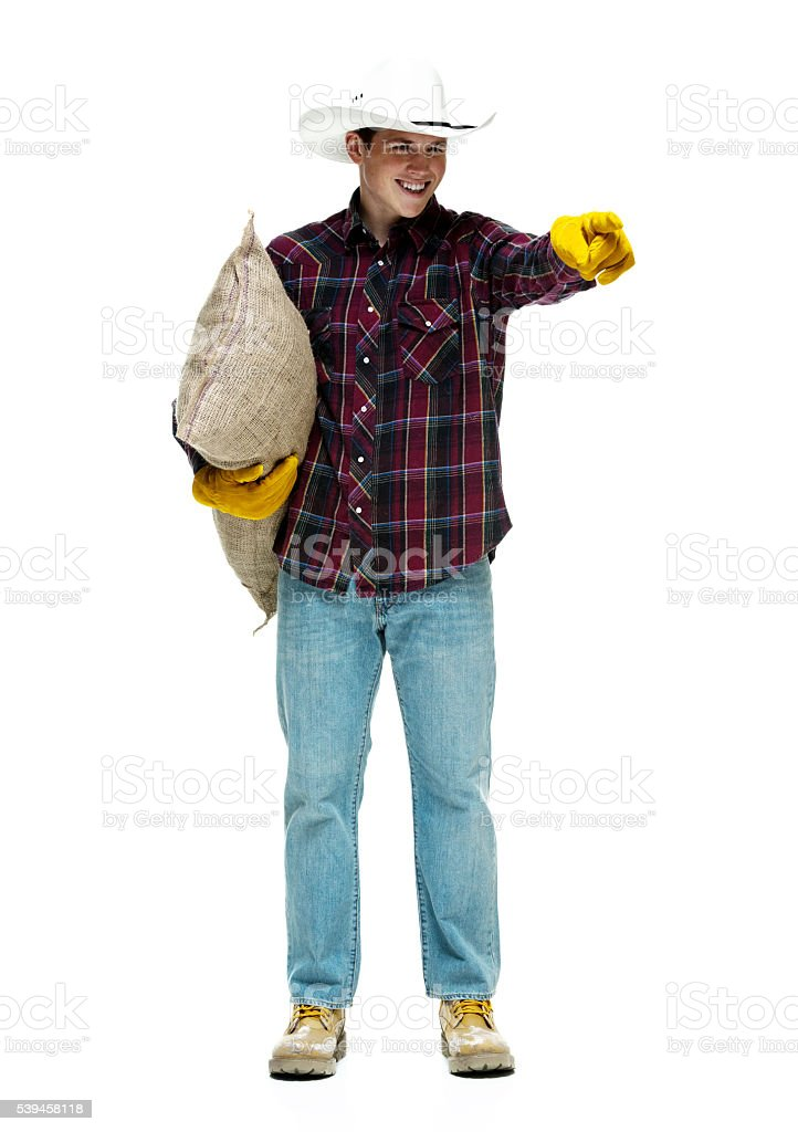 Cheerful farmer pointing away stock photo