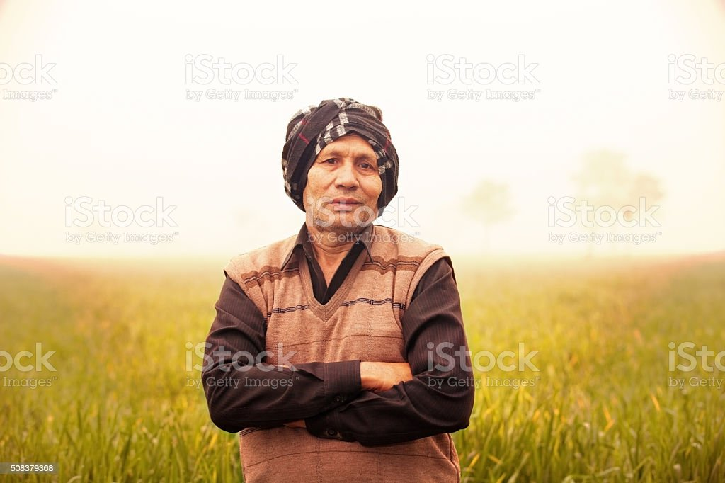 Cheerful Farmer Standing in Green Field stock photo