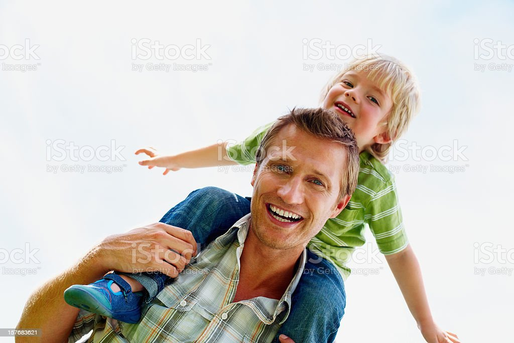 Cheerful father carrying his son on shoulders against sky royalty-free stock photo