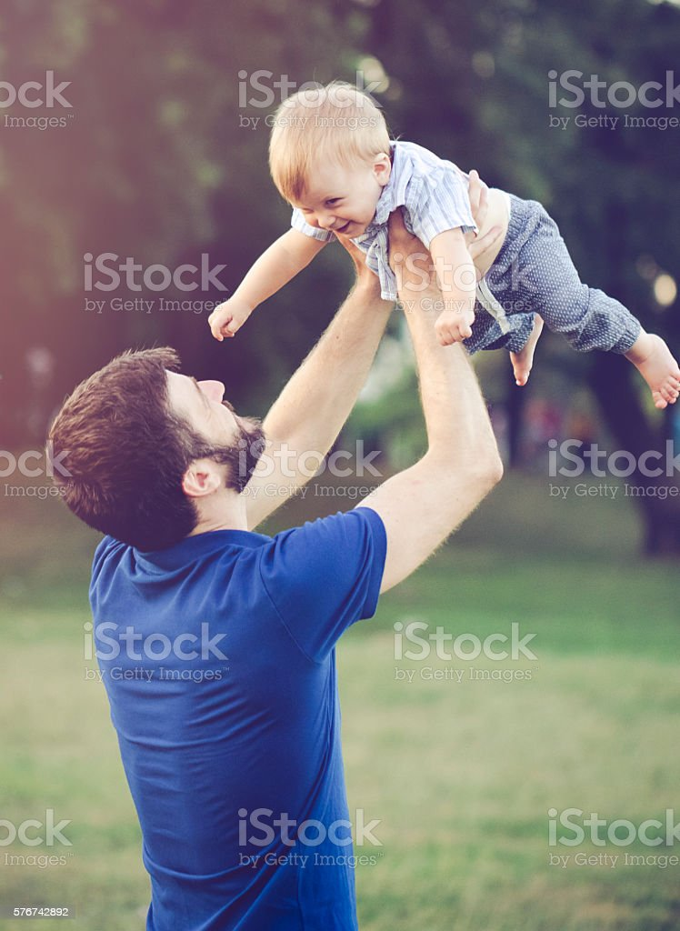Cheerful father holding aloft his son outdoors in nature stock photo