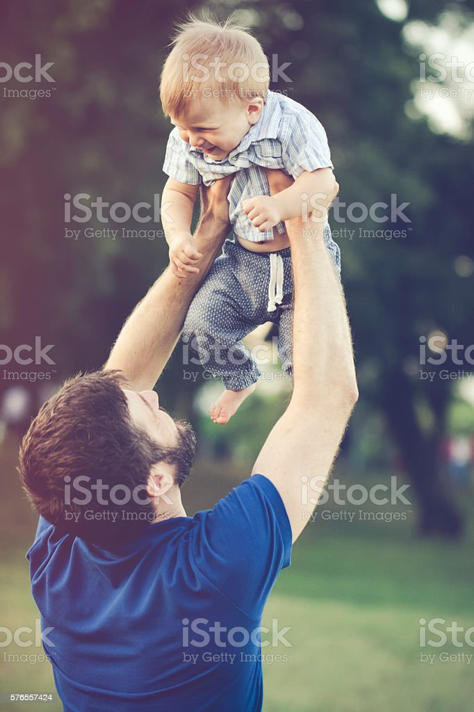 Cheerful father holding his son outdoors in nature stock photo