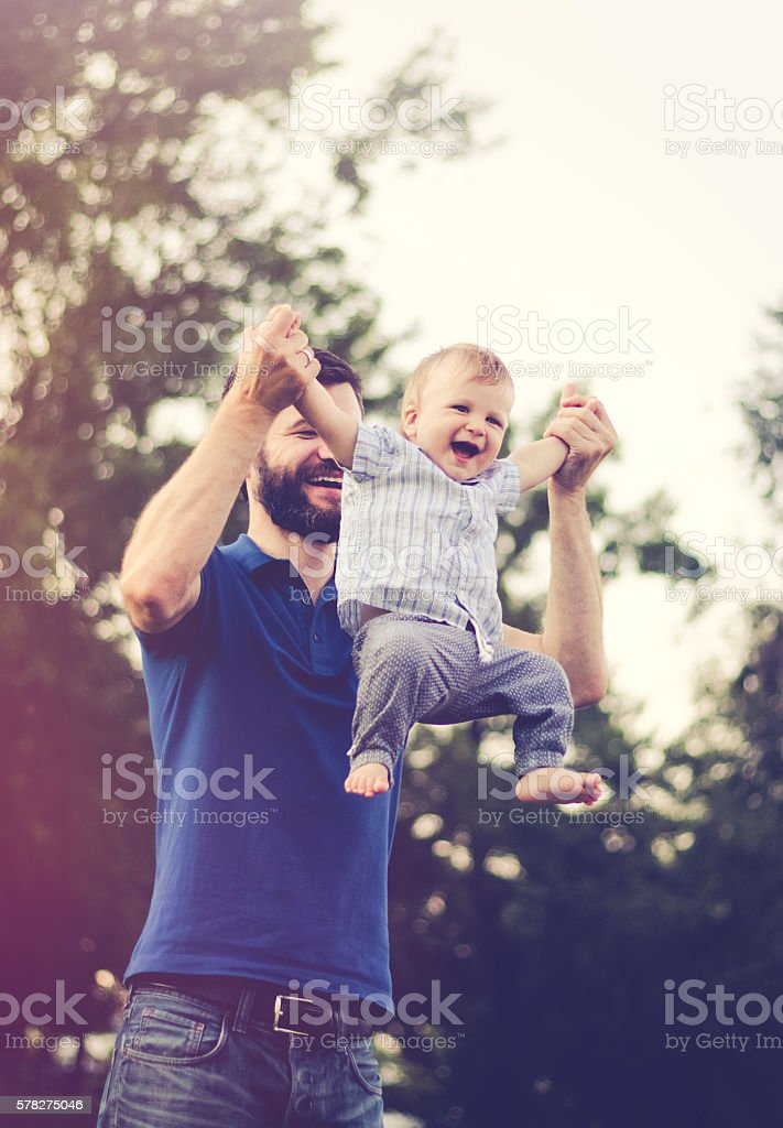 Cheerful father throwing his son in the air in nature stock photo