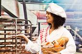 Cheerful female baker presenting in bakery