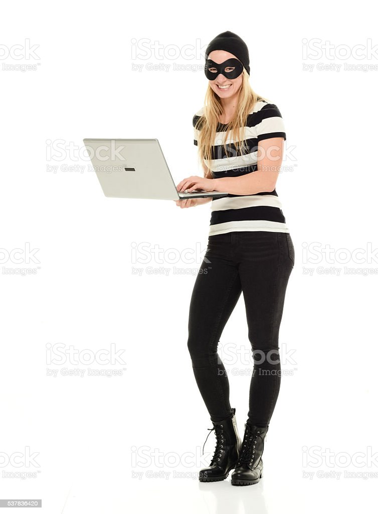 Cheerful female burglar working on laptop stock photo