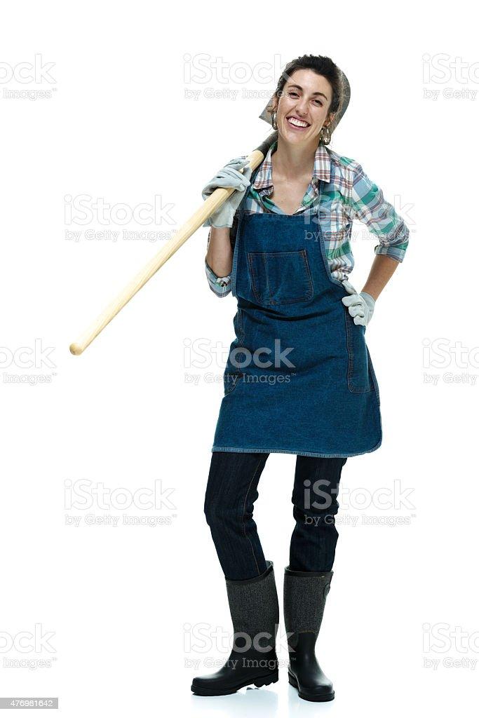 Cheerful female farmer holding shovel stock photo