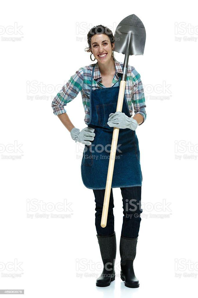 Cheerful female gardener holding shovel stock photo