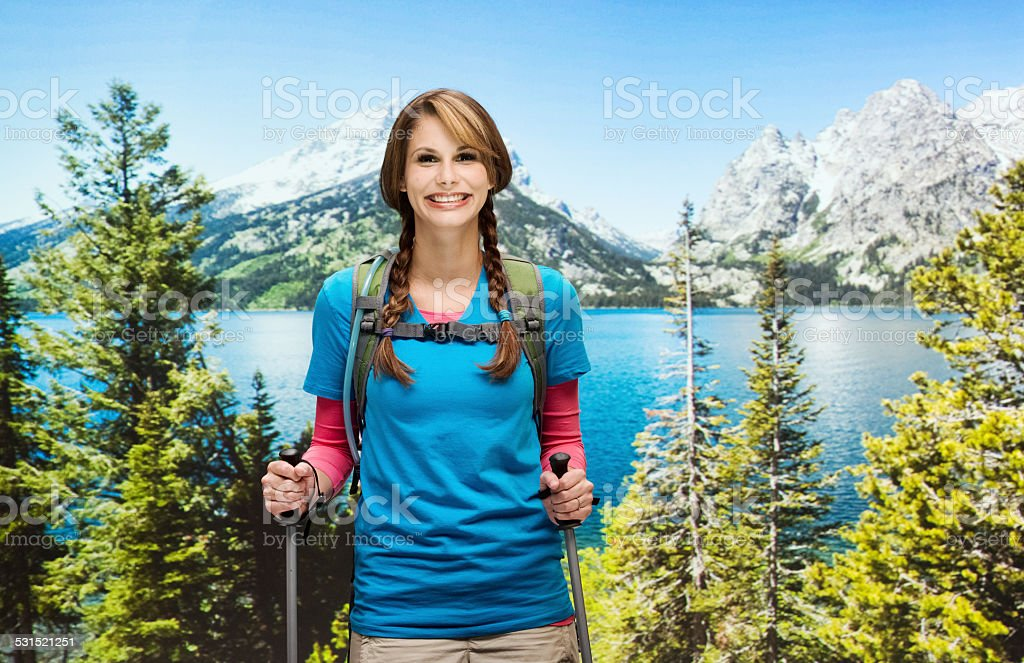 Cheerful female hiker with hiking poles stock photo