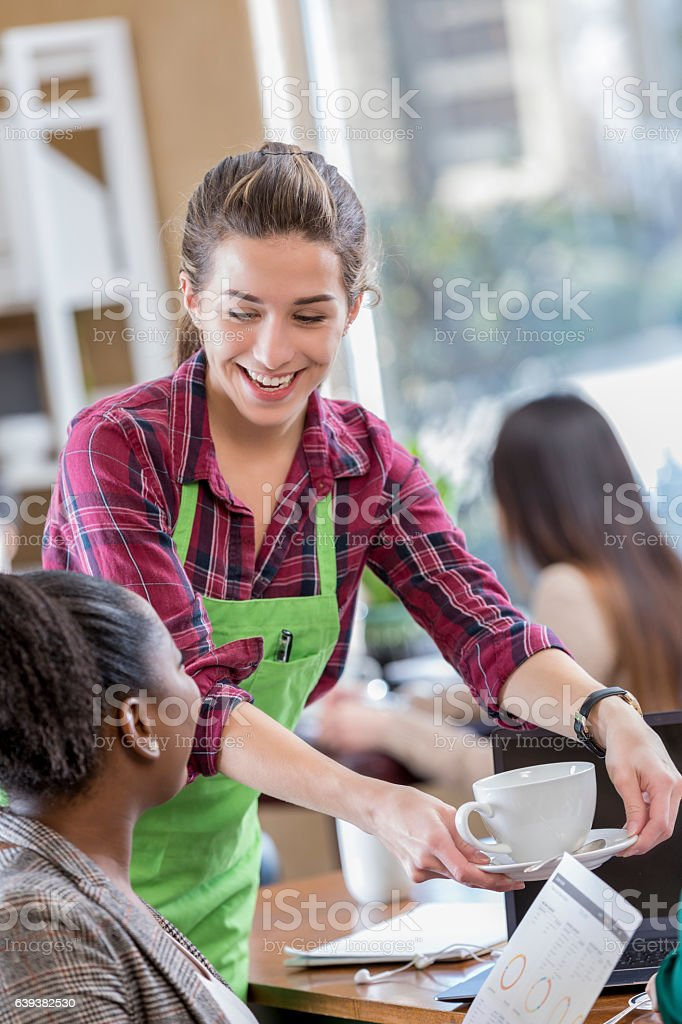 Cheerful female server serves coffee to business woman stock photo