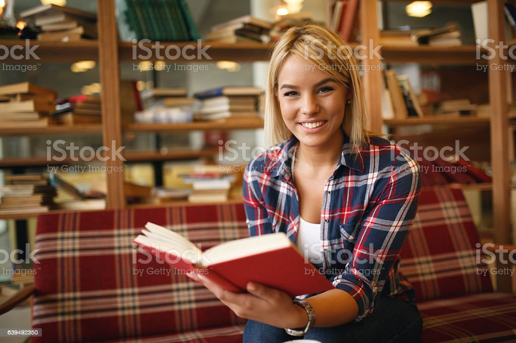 Cheerful female student enjoying book reading in library. stock photo