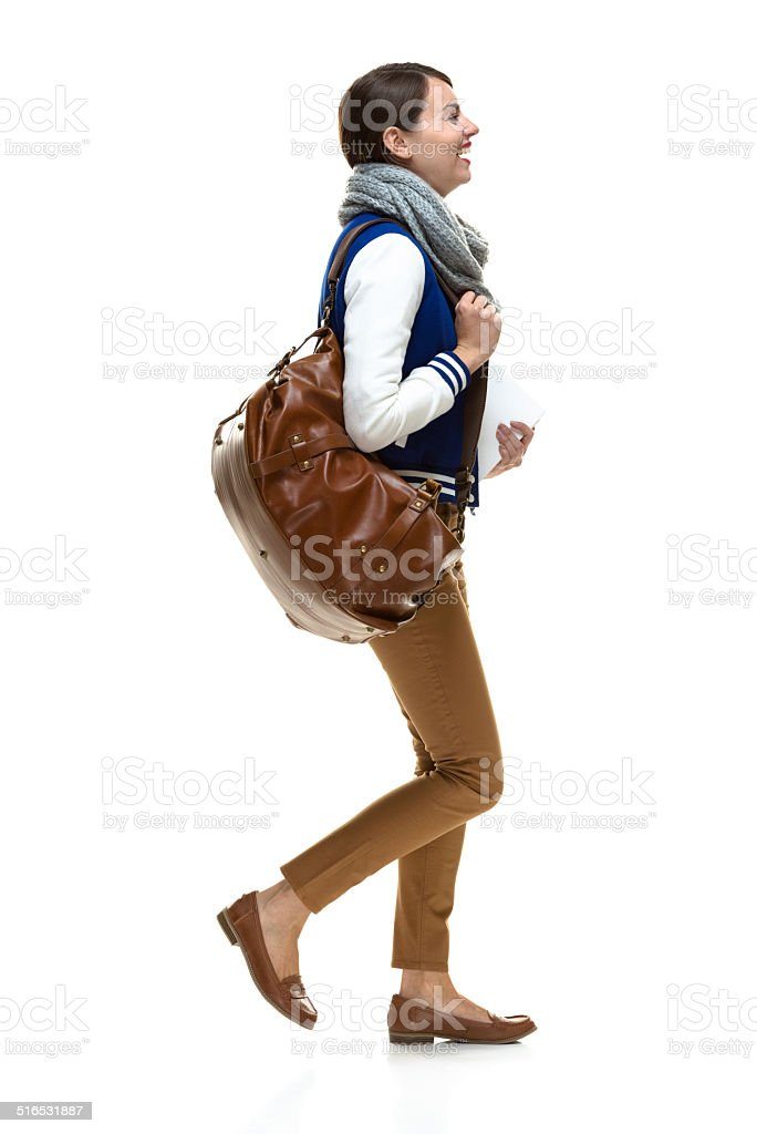 Cheerful female student holding book & walking stock photo