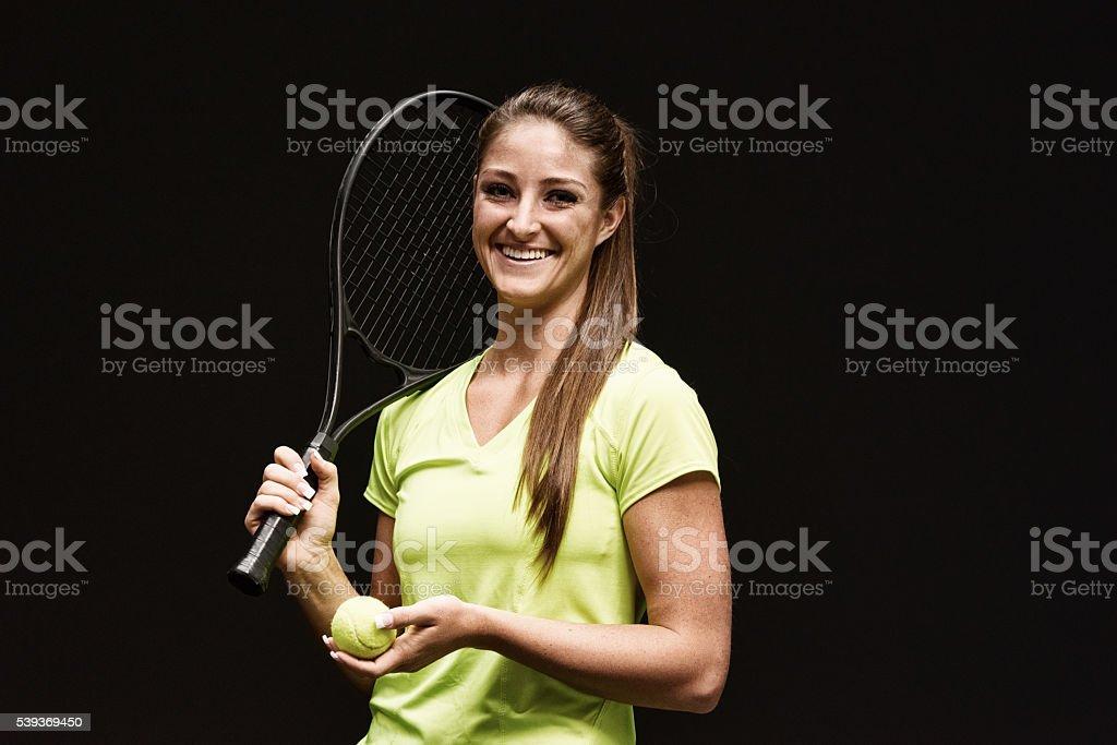 Cheerful female tennis player holding ball stock photo