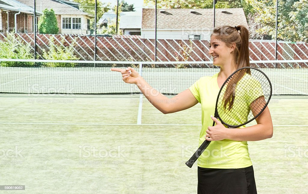 Cheerful female tennis player pointing away stock photo