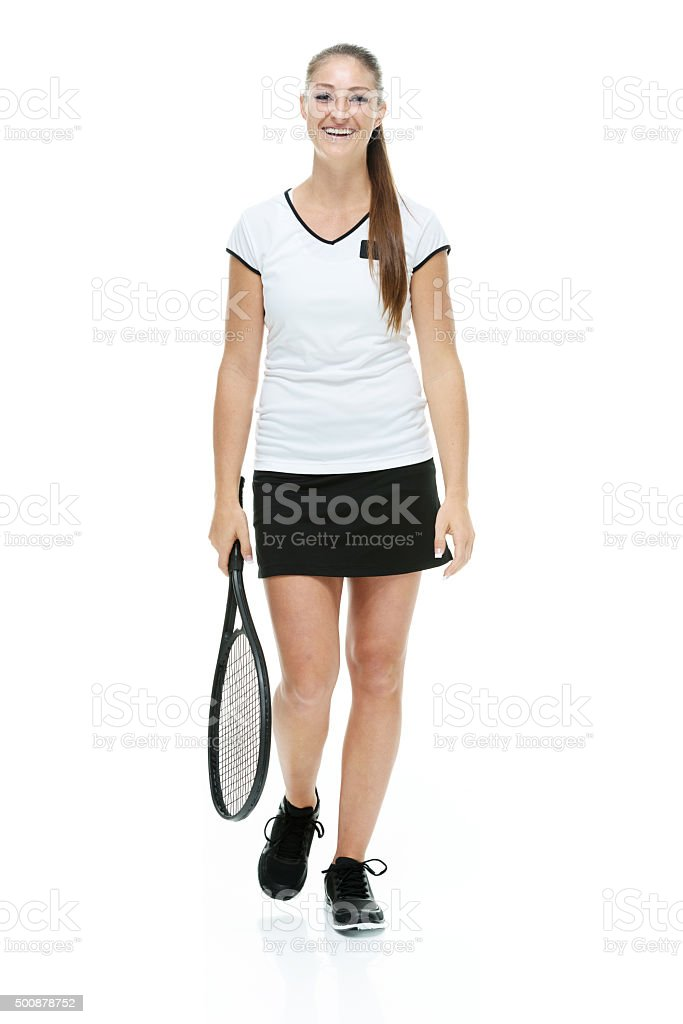Cheerful female tennis player walking stock photo