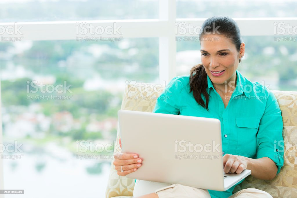 Cheerful female using laptop at home stock photo