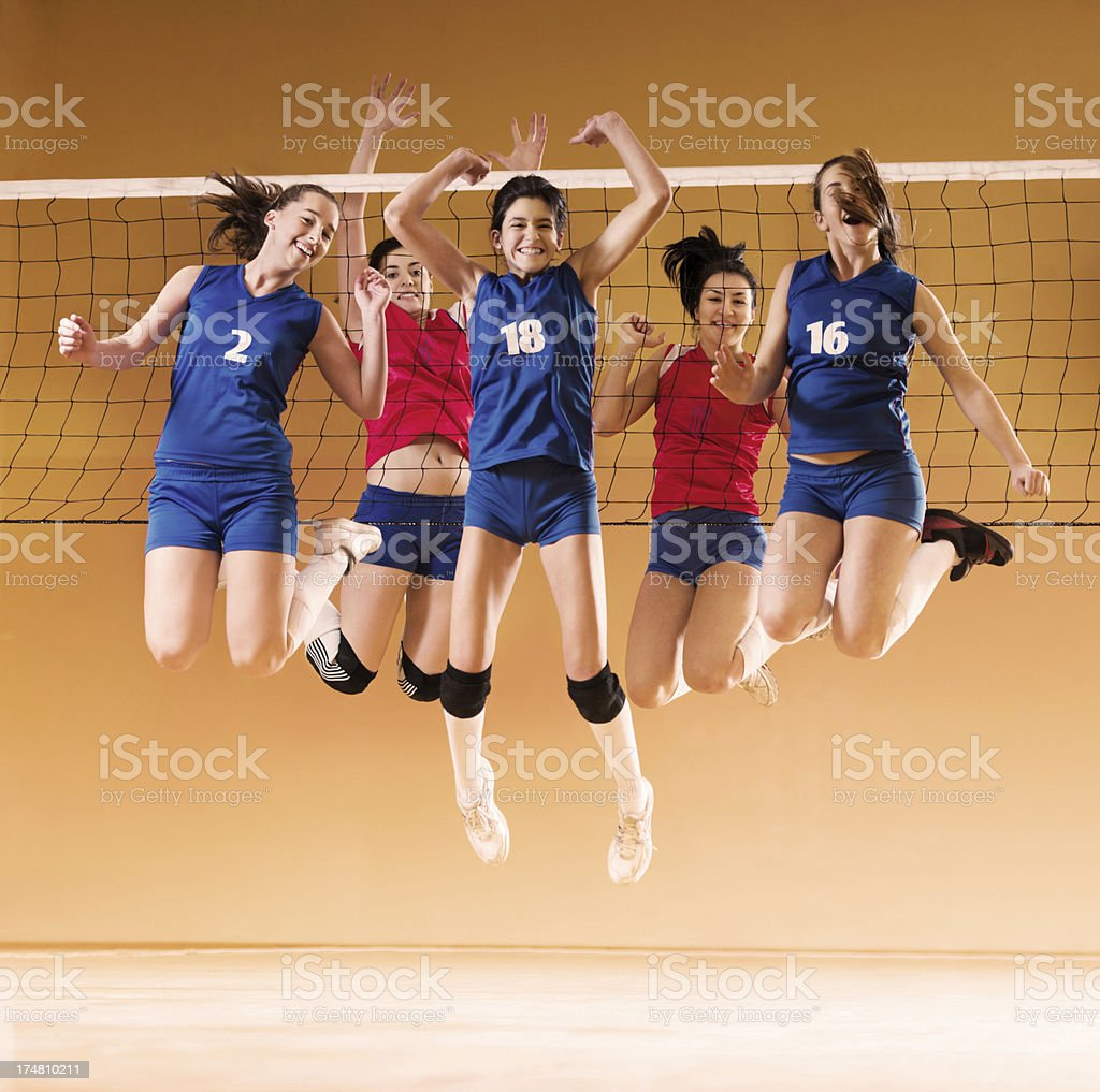 Cheerful female volleyball team jumping. stock photo