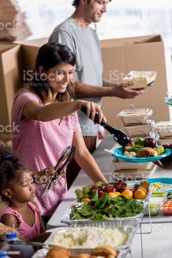 Cheerful female volunteer serves healthy meal in soup kitchen stock photo