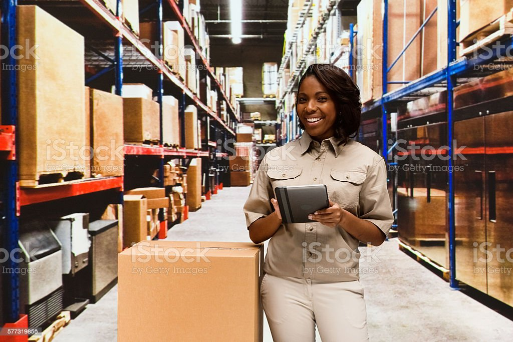 Cheerful female worker using tablet in warehouse stock photo