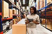 Cheerful female worker using tablet in warehouse