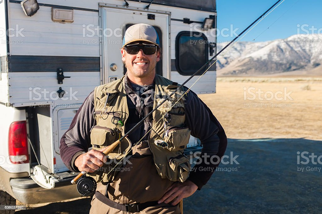 Cheerful Fly Fisherman In Front Of Camper stock photo