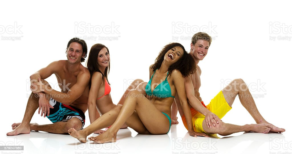 Cheerful four friends sitting on floor stock photo