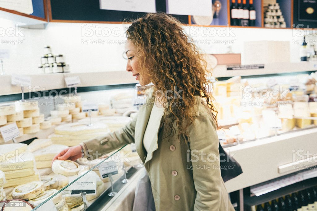 Cheerful french woman shopping cheese in a supermarket stock photo