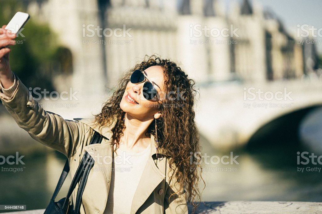 Cheerful French Woman Taking A Selfie in Paris stock photo