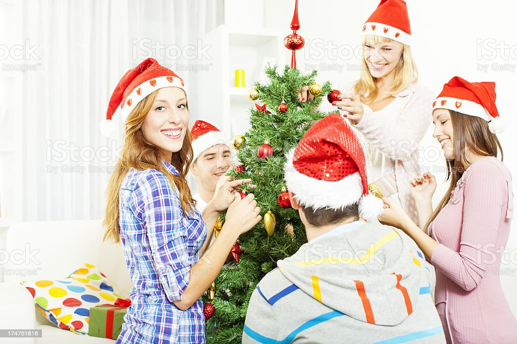 Cheerful Friends Decorating Christmas Tree. royalty-free stock photo
